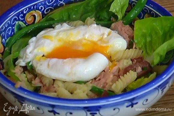 Выложить в салатницу немного листьев салата, затем макароны с тунцом и оставшийся салат, сбрызнуть оливковым маслом, а сверху поместить яйцо пашот, слегка разломив его вилкой.