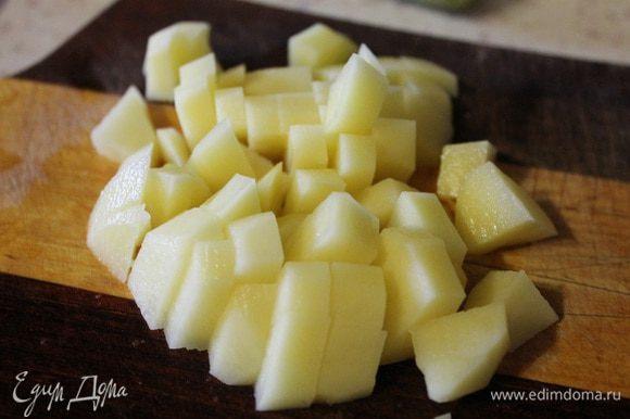 Картофель режем кубиком и кладем в бульон. Варим картофель 15 минут, потом добавляем рис.