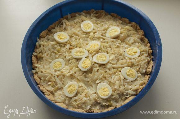 Начинку распределить по коржу в форме. Сверху разложить отварные яйца, нарезанные на части. Выпекать пирог в духовке при 180-200 гр. 30 минут.