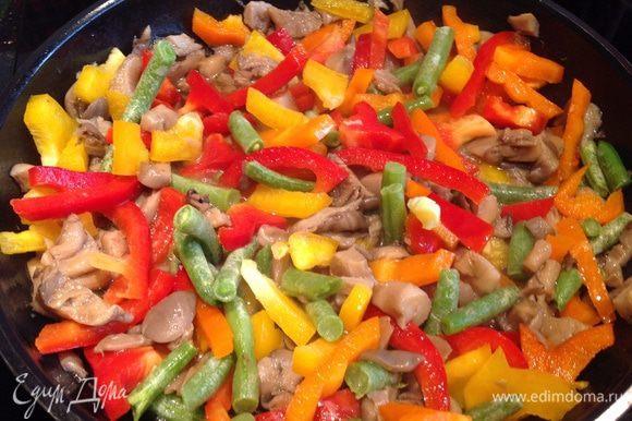 Добавьте к грибам 1 ст л оливкового масла, перец, фасоль (не размораживая, если она была заморожена), выдавленный прессом чеснок. Накройте крышкой и тушите на среднем огне около 4 минут.