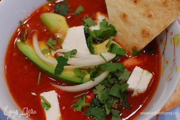 Суп разлить в тарелки, в каждую добавить по 2 кусочка авокадо, маринованный лук и кусочки феты, посыпать кинзой и подавать с кусочками тортильи.