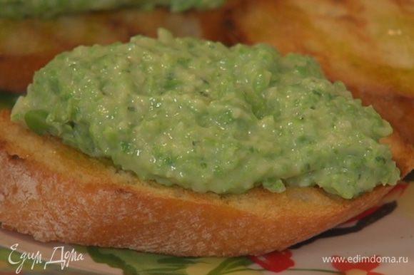 Поджаренный хлеб сбрызнуть оставшимся оливковым маслом и разложить сверху взбитый горошек.