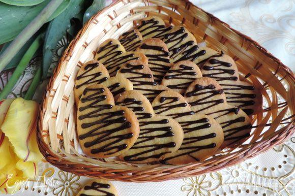 Остывшее печенье украшаем растопленным с молоком шоколадом при помощи кондитерского мешочка или плотного пакетика (файла) со срезанным уголком.