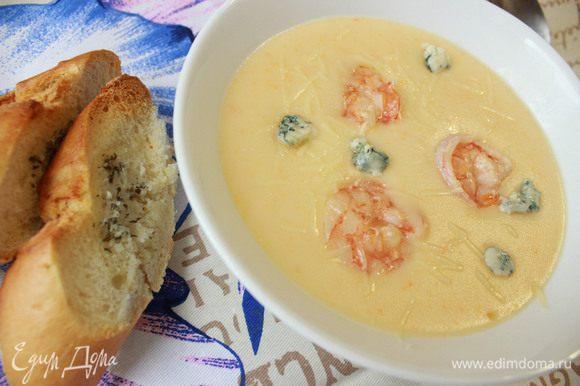 В глубокую тарелку налейте суп. Аккуратно выложите креветки. Посыпьте тертым пармезаном. Добавьте немного сыра данаблю. Подавайте крем-суп со свежим багетом. Приятного аппетита!