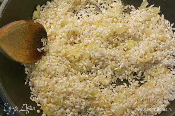 Следите, чтобы лук не зажарился! Как только лук посветлеет, всыпать рис. Перемешать и дать обжариться вместе с луком 1-2 минуты, помешивая.