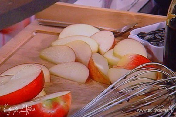 Листья салата вымыть, высушить, разложить на тарелки. Яблоки (желательно плотные, кисло сладкие и красные) порезать дольками. Смешать тыквенное масло с тёмным балзамиком, мёдом и солью.