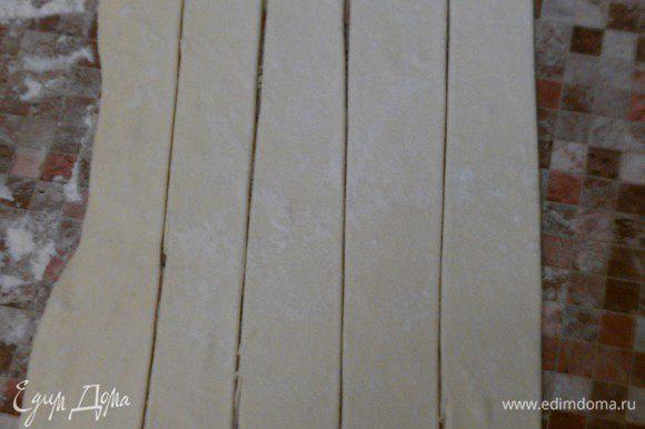 Размороженное тесто тонко раскатать (1-2 мм по толщине). Порезать на полоски 3 см по ширине и 30 см по длине.