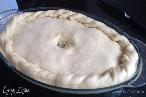 Раскатайте вторую часть тестами накройте ею пирог. Подрежьте края оставив свисать примерно 2 см теста. Расправьте края и красиво загните складками по краю пирога. В центре получившейся крышечки из теста сделайте небольшое отверстие.