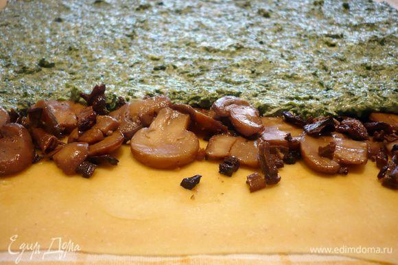 Тесто делим на две части. Одну часть заворачиваем в пленку. Другую раскатываем на припыленной мукой поверхности в тонюсенький пласт в 40 на 30 см. Кладем пласт на полотенце. Отступив примерно 3 см от края выкладываем полоску ½ грибной начинки, разравниваем, оставляя свободные края справа и слева. Следом за грибами распределяем ½ шпинатной начинки.
