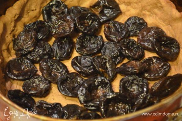 На испеченный корж выкладываем чернослив (при этом остатки жидкости с него надо слить).