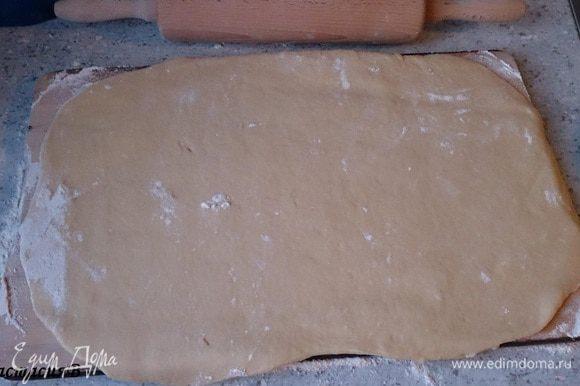 Раскатать тесто прямоугольной формы на посыпанной мукой поверхности.