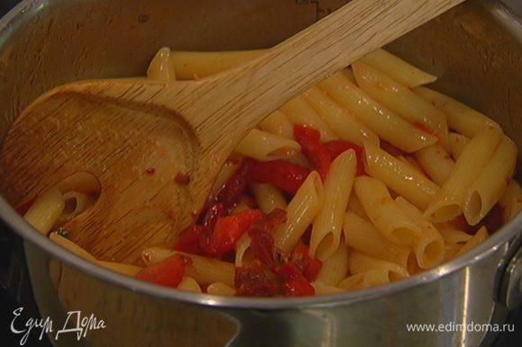 В кастрюлю с горячими макаронами добавить вяленые помидоры, черри и сладкий перец, поставить кастрюлю на небольшой огонь, сбрызнуть все оливковым маслом, перемешать и немного прогреть.
