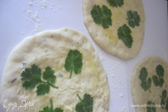 Разделить тесто на 5 - 6 частей и раскатать в круг. Накрыть полотенцем и оставить на 15 минут. Включить духовку. После чего, смазать лепешки растопленным сливочным маслом. Посыпать зеленью и зирой, чуть-чуть придавить зелень, можно скалкой. Выложить на противень. Выпекать 20-25 минут, при температуре 180 С. Смазать готовые лепешки растопленным маслом.