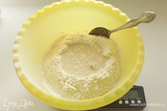 Насыпать муку в большую миску,сделать в ней углубление. Насыпать дрожжи,добавить к ним сахар и 70 мл теплой воды.
