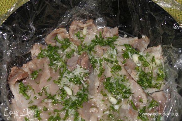На кожу выкладываем половину начинки чеснок с зеленью. Затем кладем мясо рульки, разобранное руками на средние кусочки.