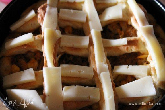 Как только пирог начнет приобретать слегка золотистый цвет, достать его из духовки. Сыр нарезать брусочками и разложить его на решетке из теста. И опять отправить в духовку на 5-8 минут..