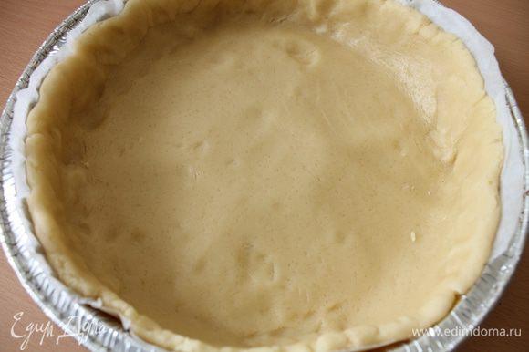Достать тесто из холодильника, отделить примерно четверть для украшения. Остальное тесто раскатать в круг на бумаге для выпечки, перенести в форму, оформить бортик.