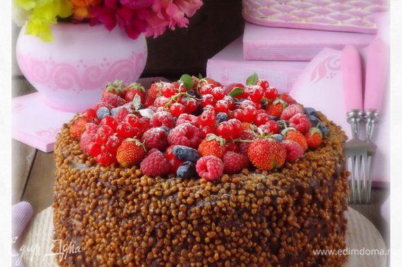 Бока торта обмазать кремом и обсыпать грецким орехом в карамели. Сверху уложить ягодное ассорти.