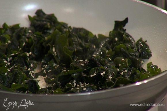 Водоросли слегка отжать (воду сохранить), добавить их в сковороду с чесноком, перемешать и посыпать кунжутными семечками.