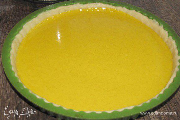 Раскатать тесто в круг по диаметру формы и с помощью скалки перенести его в форму. Сформировать бортики. Наколоть тесто вилкой. Вылить на тесто тыквенную начинку и разровнять.