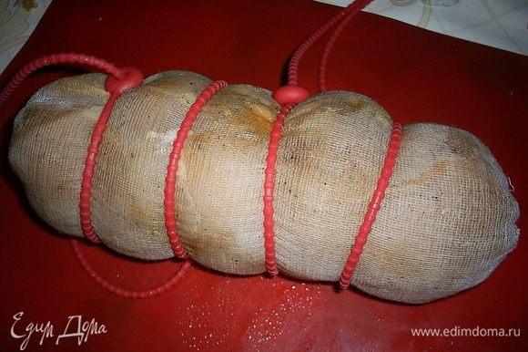 """По истечению нужного времени достаем грудку, обсушиваем бумажными полотенцами. Натираем грудки пропущенным через пресс чесноком. Берем марлю, сворачиваем ее в три слоя, затем с ее помощью сворачиваем грудки """"колбаской"""" как можно туже. Несколько раз перевязываем бечевкой или воспользуемся специальными силиконовыми шнурочками."""