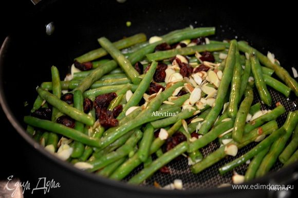 На горячую сквороду вылить оливковое масло, затем орехи и клюкву сушеную. Добавить фасоль, посолить и поперчить. Перемешать.