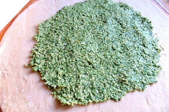 Делим тесто пополам (или больше), каждую часть тонко раскатываем, кладём половину всей начинки, размазываем по центру. На доску понадобится ещё около полстакана муки.