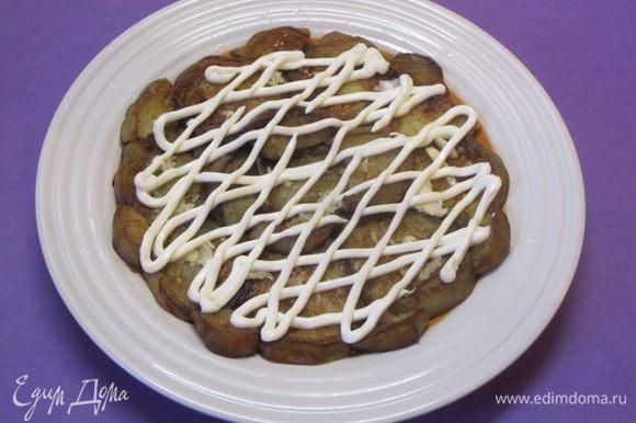 На плоскую тарелку выложить половину остывших обжаренных баклажанов. Сверху выложить тертый чеснок, смазать майонезом.