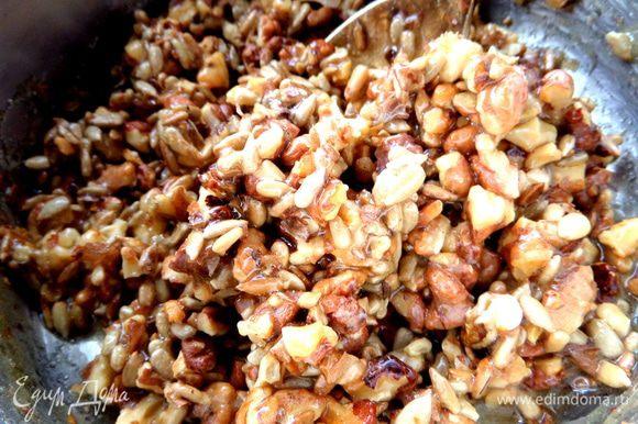 Высыпать обжаренные орехи, семечки, быстро перемешать.
