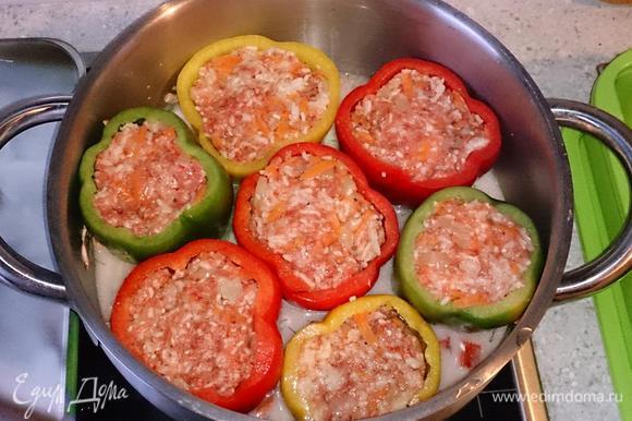 Выложить фаршированные перцы. Долить воды, чтобы перцы наполовину были в соусе.