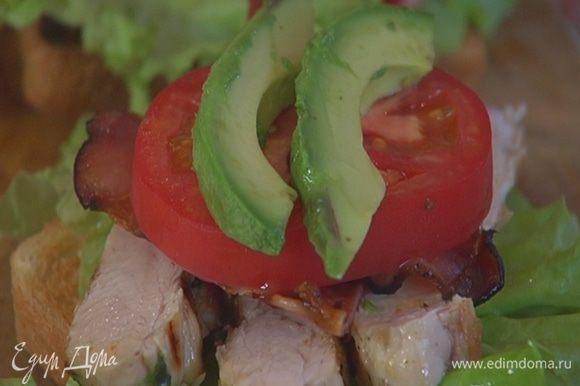 На три тоста выложить куриное мясо, бекон, кружок помидора и авокадо.