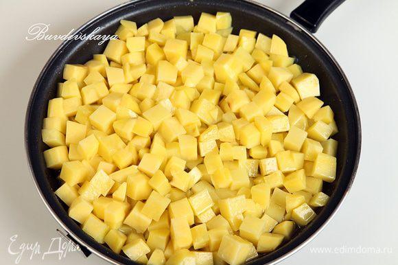 Картофель вымыть, очистить и нарезать кубиками со стороной в 1 см. В сковороде разогреть растительное масло. Не переживайте, что его слишком много: чем больше будет в сковороде масла, тем меньше его в себя впитает картофель, а излишки мы потом сольем. Выложить в сковороду картофель и уменьшить огонь до минимального. Периодически картофель необходимо помешивать лопаткой. Томить до готовности картофеля: он должен стать мягким. Внимание: нам не нужно поджарить картофель до золотистой корочки, нам нужен именно томленный картофель. Это занимает довольно много времени.