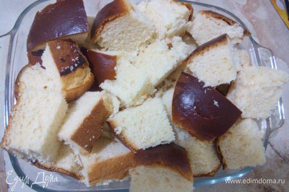 Для данного пудинга нам понадобится немного сладкий хлеб. У нас продаются большие булочки, они еле сладкие, я взяла таких 4 штуки и порезала на квадратики. Форму смазываем сливочным маслом и выкладываем хлеб.