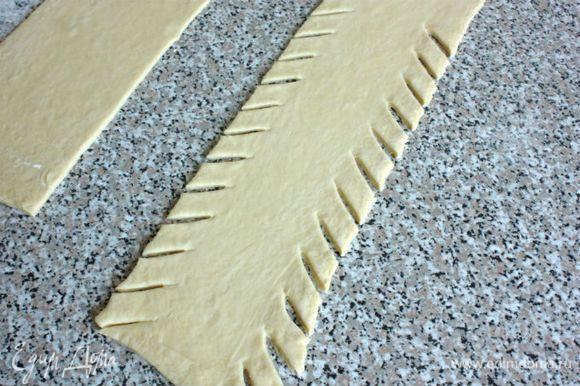 С краёв к центру под углом нарезать тесто полосками в 2 см шириной и 4 см длиной.