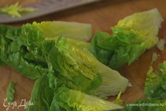 Салат романо разрезать на 4 части, выложить на большую тарелку и полить половиной заправки.