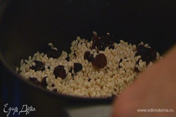 В глубокой кастрюле растопить 1 ст. ложку сливочного масла, всыпать рис и дать ему пропитаться маслом 1–2 минуты, затем добавить изюм, перемешать и прогреть еще немного.