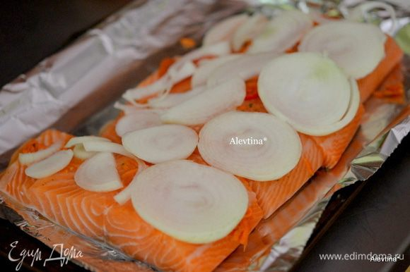 Тонко нарезать луковицу, выложить поверх рыбы.
