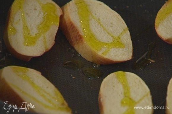 Багет нарезать, выложить на противень, сбрызнуть оливковым маслом и отправить в духовку под гриль на 2–3 минуты.