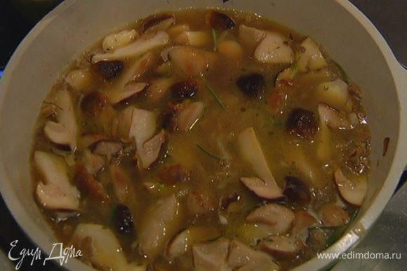 Добавить размороженные грибы, немного посолить, посыпать листьями розмарина и тимьяна, влить воду, в которой замачивались сухие грибы, куриный бульон, все перемешать и готовить минут 10.