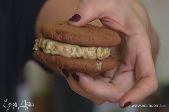 Из готового мороженого кондитерским кольцом вырезать кружок, выложить на одно печенье и накрыть вторым, чтобы получились сэндвичи.