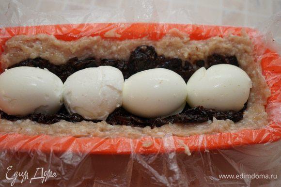 На него кладём подготовленные яйца, стараясь, чтобы они оказались в центре рулета, а промежутки между ними были заполнены черносливом.
