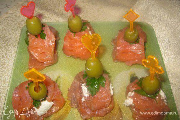 На каждый ломтик рыбы кладем по 1 столовой ложке творожной массы и сворачиваем в рулетик. На шпажку накалываем оливку, петрушку и рулетик. Приятного аппетита!