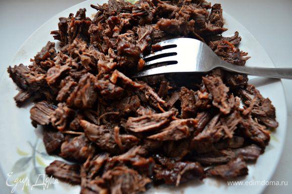 С помощью вилки разобрать мясо на волокна.