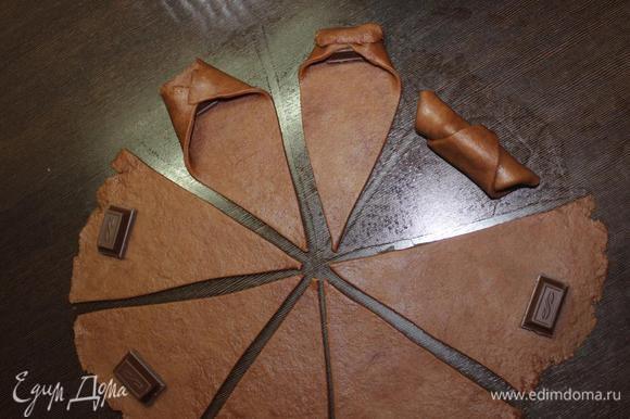 На широкий край выкладываем кусочек шоколада, загибаем края к центру и сворачиваем в рулет к узкому краю.