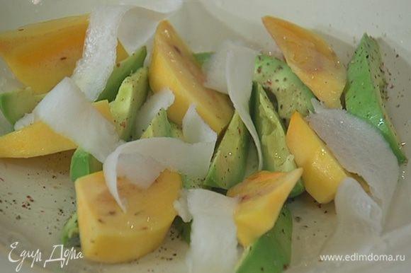 Дайкон почистить, нарезать тонкими полосками (можно воспользоваться овощечисткой) и выложить на хурму с авокадо, затем добавить салатные листья.