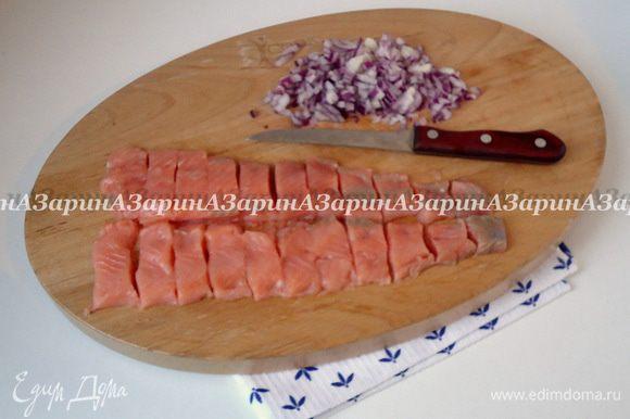 Приготовить начинку. Филе красной рыбы посолить, поперчить и разрезать на сегменты шириной по 2.5-3 см. Лук очистить и нарубить мелкими кубиками.