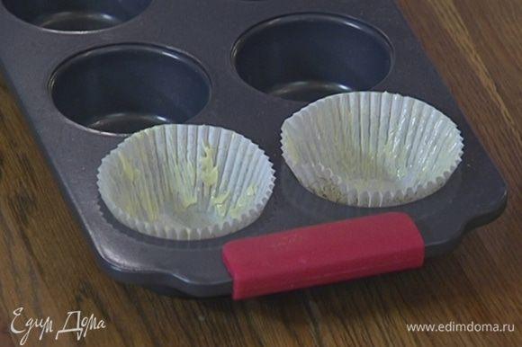 Бумажные вкладыши для кексов смазать оставшимся сливочным маслом и вложить их в формочки.