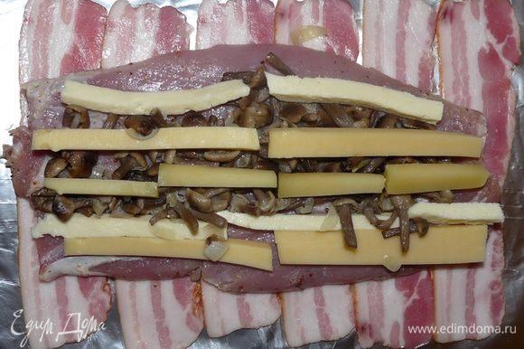 Выложить на фольгу полоски бекона. На бекон положить пласт вырезки. На пласт выложить рядами начинку.