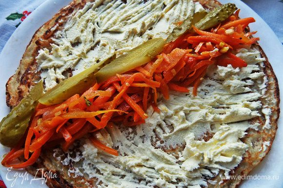 Укладываем лентой пару ложек морковки по-корейски и маринованный огурчик нарезанный.