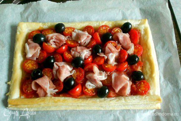 Достаньте из духовки заготовку и разложите ветчину и оливки. Запекайте ещё 5 минут.